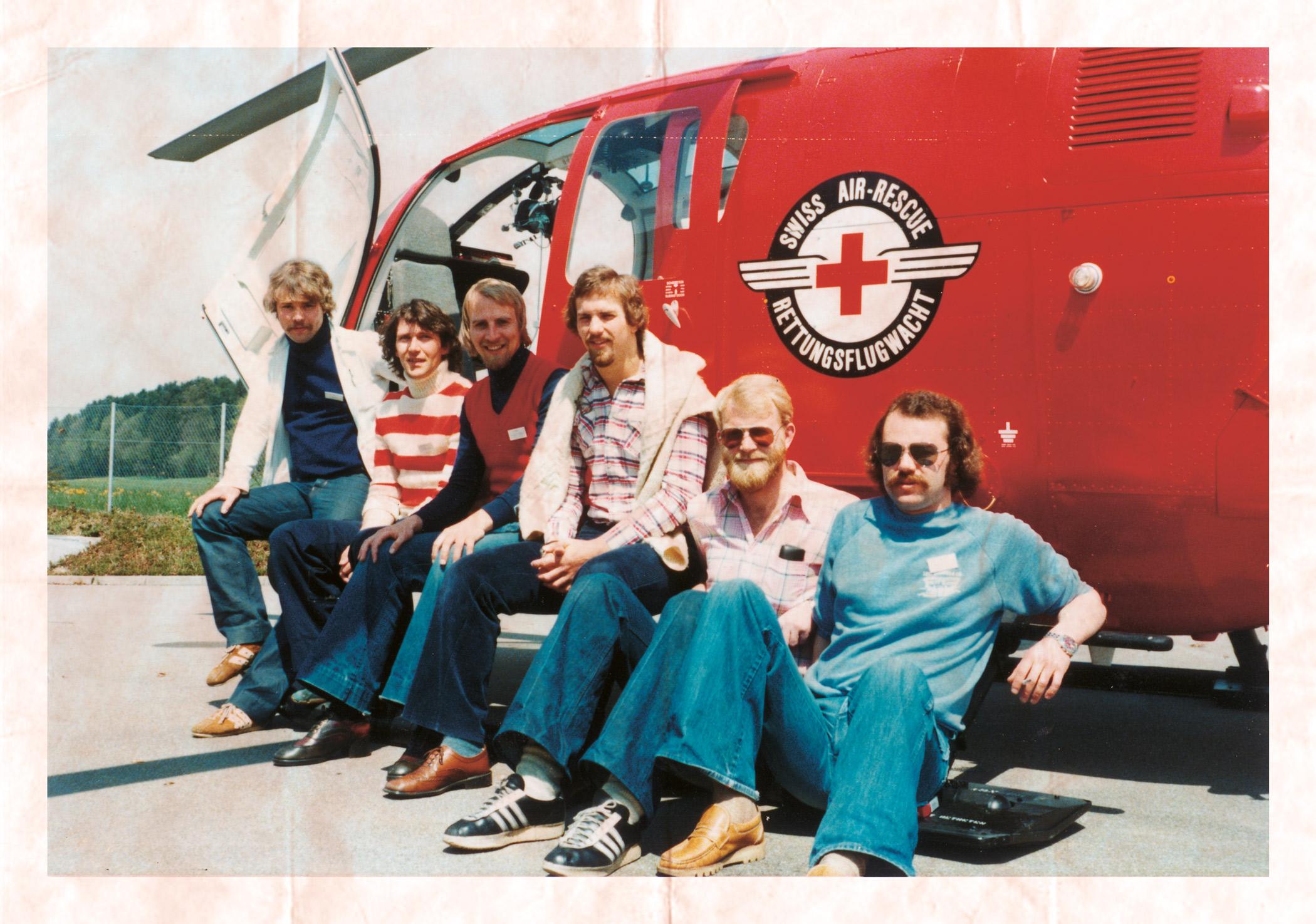 Seks nordmenn sitter foran sveitsisk helikopter.