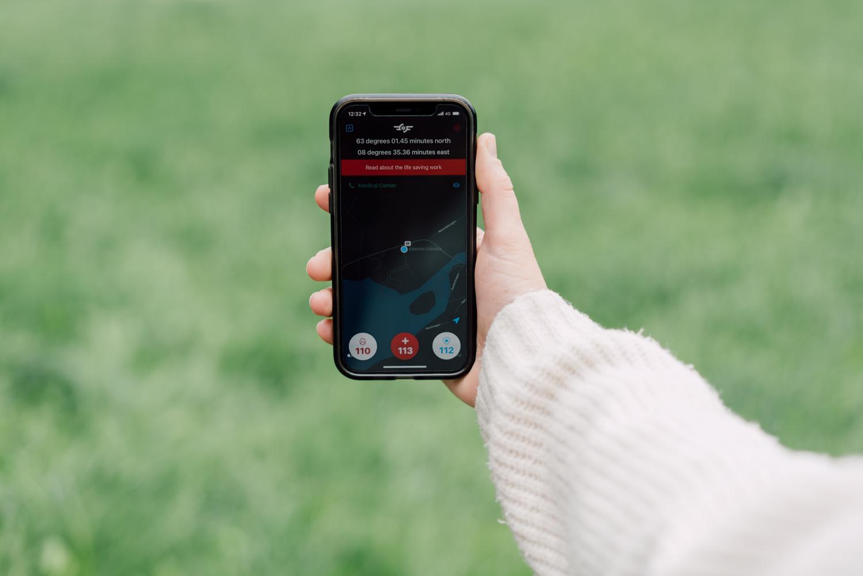 Person som holder opp smarttelefon med appen «Hjelp 113» åpen. Appen viser et kart og koordinater for posisjon, samt ringeikoner til nødetatene.
